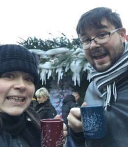 Me and husband at the Christmas market in Dresden, Germany holding mugs of hot mulled wine
